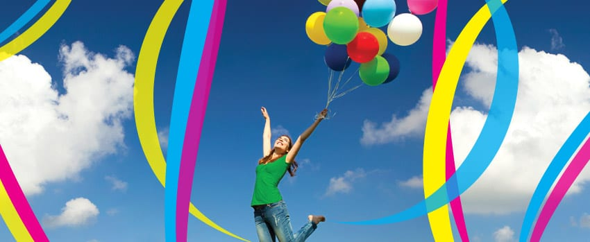 Woman jumping with balloons with a blue sky background