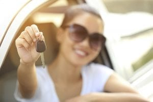 Happy woman in driver's seat holding out a car key