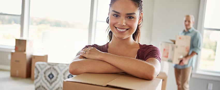 Young couple moving boxes into new home