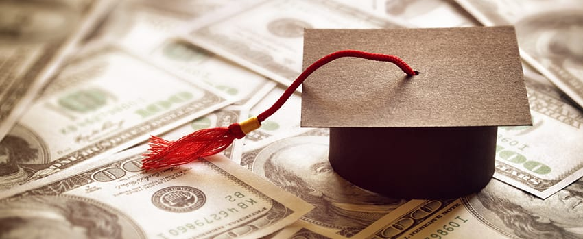 graduation cap on money pile
